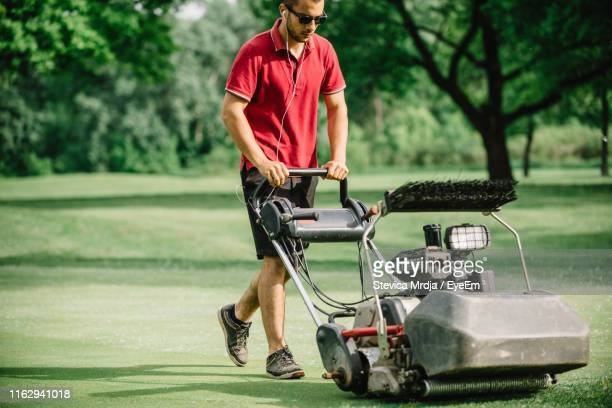 full length of man mowing grassy land with lawn mower - ground staff stock pictures, royalty-free photos & images
