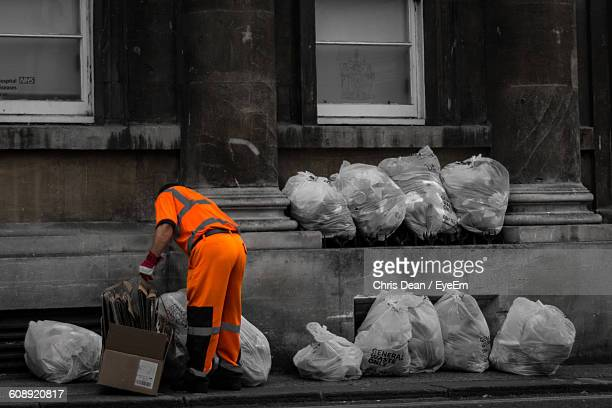 full length of man of collecting garbage from street - street sweeper stock pictures, royalty-free photos & images