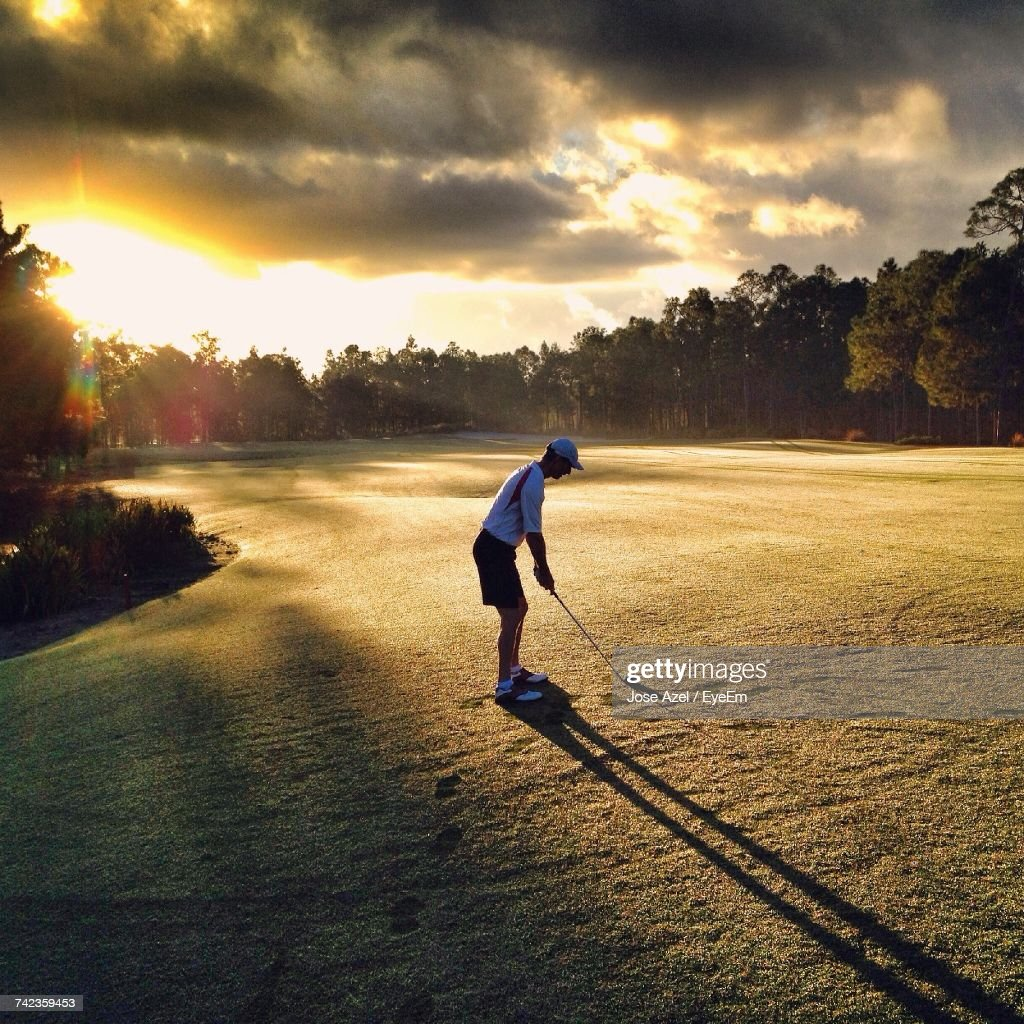 Full Length Of Man On Golf Course Against Sky During Sunset : Stock Photo