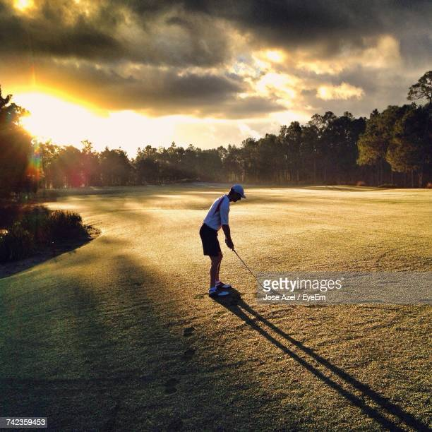 Full Length Of Man On Golf Course Against Sky During Sunset