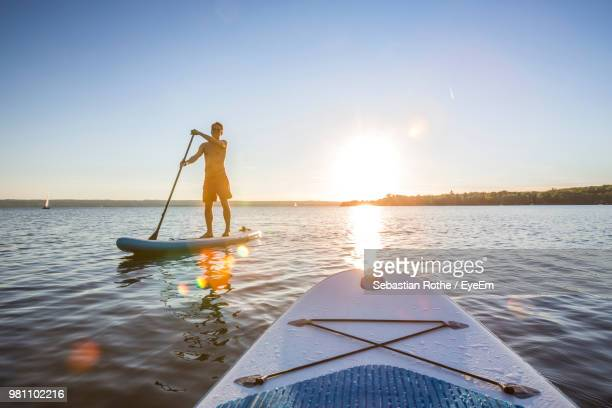 full length of man on paddle board in sea during sunset - paddleboard stock pictures, royalty-free photos & images