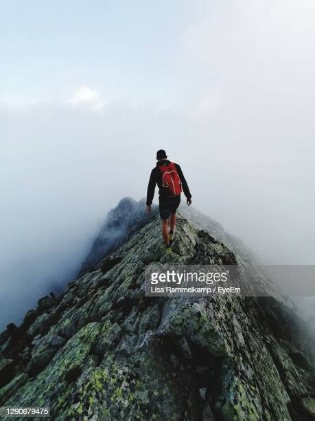 full length of man on rock in mountains - danger stock pictures, royalty-free photos & images