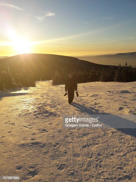 Full Length Of Man On Snow Covered Field Against Sky During Sunset