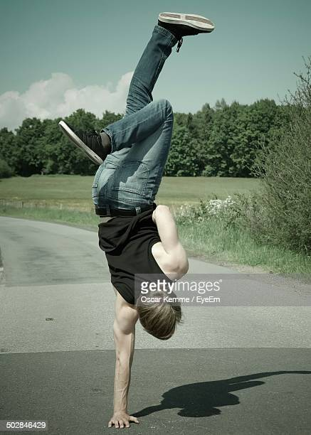 Full length of man performing handstand on street