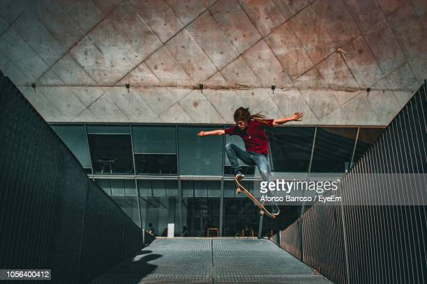full length of man performing stunt in skateboard park - skating stock pictures, royalty-free photos & images