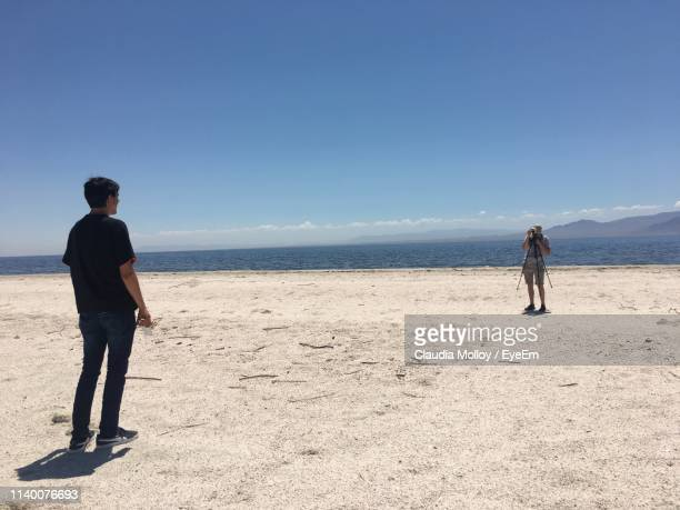 full length of man photographing friend while standing at beach against sky during summer - sandy molloy stock photos and pictures