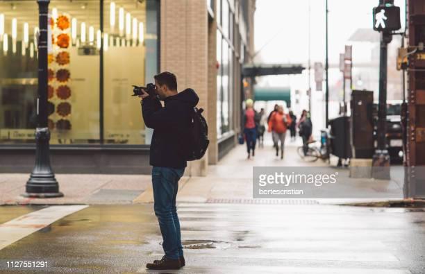 full length of man photographing in city - bortes imagens e fotografias de stock