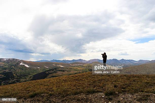 Full Length Of Man Photographing On Mountain Against Cloudy Sky