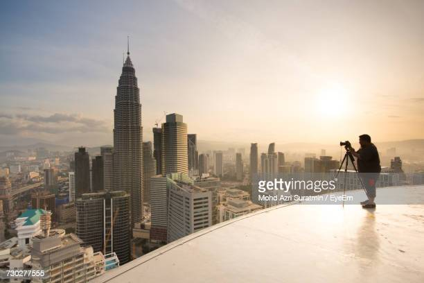 full length of man photographing skyscrapers on building terrace using camera against sky - petronas towers stock pictures, royalty-free photos & images