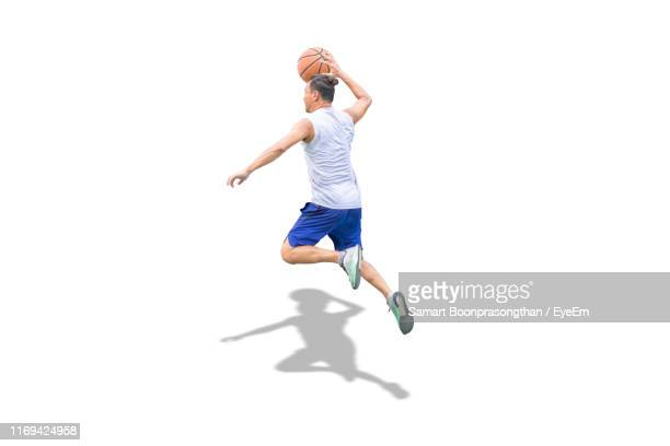 full length of man playing basket ball against white background - basketball player stock pictures, royalty-free photos & images