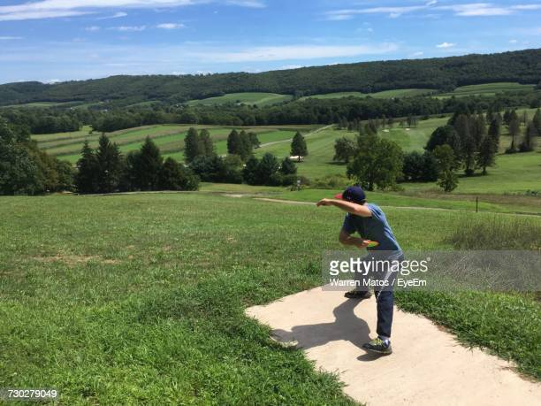 Full Length Of Man Playing Disc Golf On Field During Sunny Day