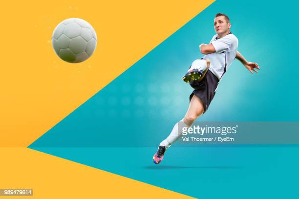 full length of man playing soccer against colored background - traje de fútbol fotografías e imágenes de stock