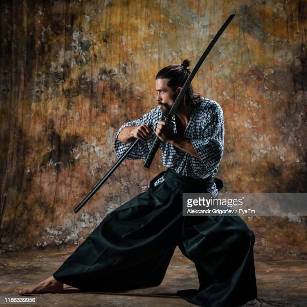 full length of man practicing ninja against wall - samurai stock pictures, royalty-free photos & images