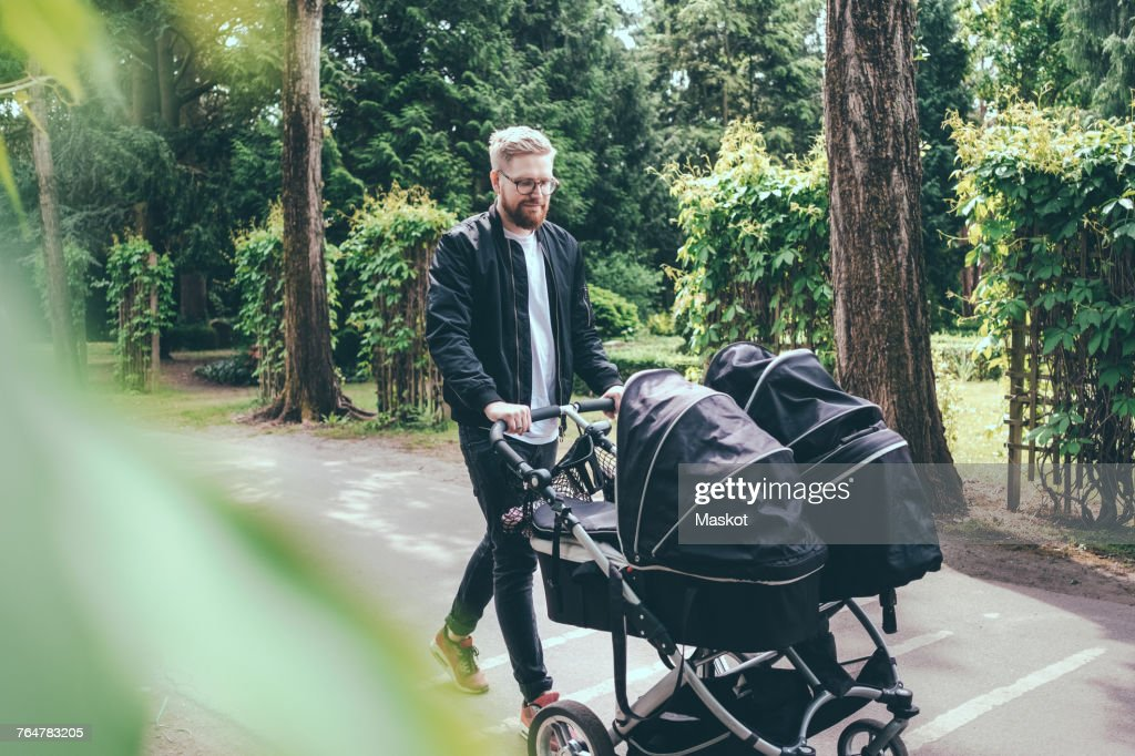 Full length of man pushing baby carriage on footpath : Stock Photo