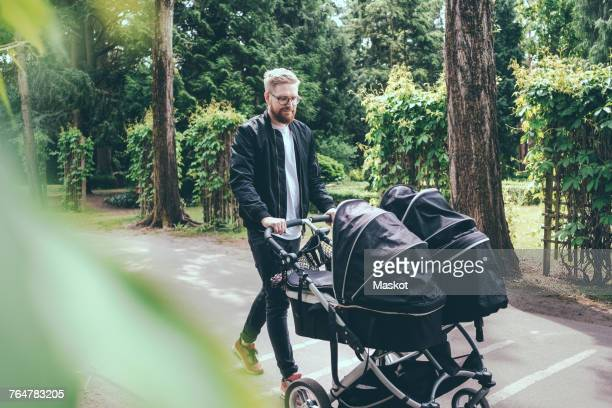 full length of man pushing baby carriage on footpath - carriage stock pictures, royalty-free photos & images