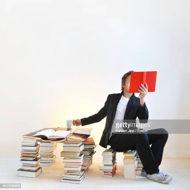 Full Length Of Man Reading Book Against Wall