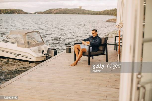 full length of man reading book while sitting on patio against lake - standing water stock pictures, royalty-free photos & images