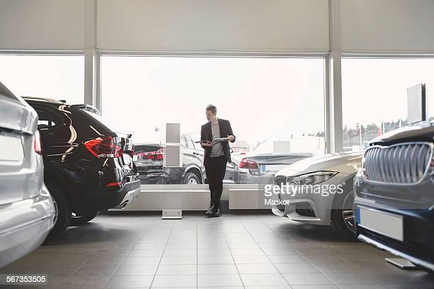 Full length of man reading brochure in car dealership store