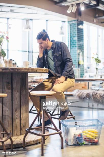 full length of man reading magazine while sitting at table in supermarket - food journal stock-fotos und bilder