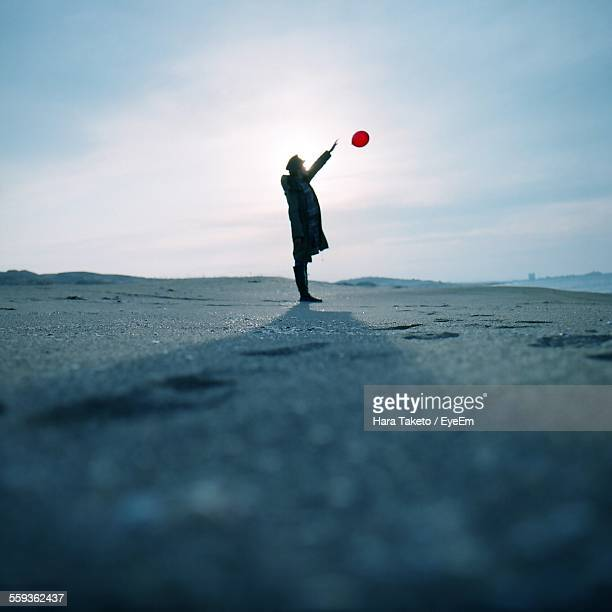 full length of man releasing balloon on beach - releasing stock photos and pictures