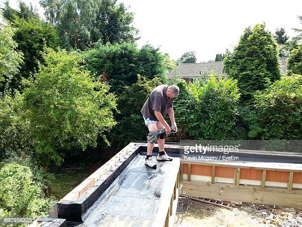 Full Length Of Man Removing Shorts On Building Terrace