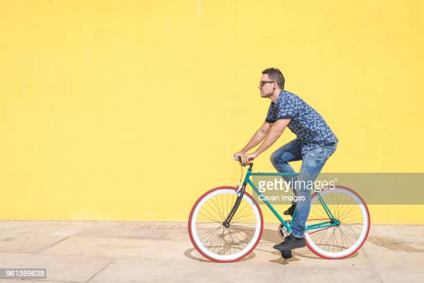 full length of man riding bicycle against yellow wall at sidewalk in city - ciclismo foto e immagini stock