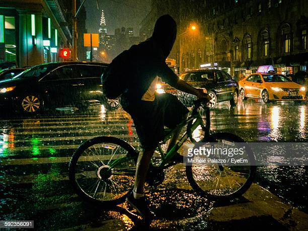 Full Length Of Man Riding Bicycle On City Street During Monsoon At Night