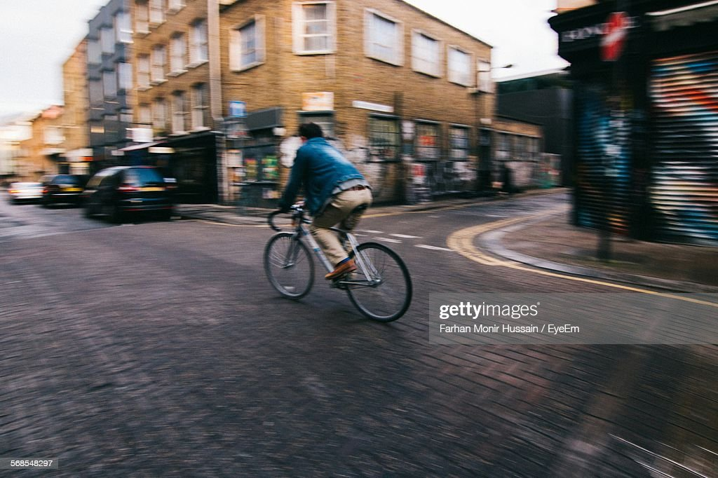 Full Length Of Man Riding Bicycle On City Street : Stock Photo
