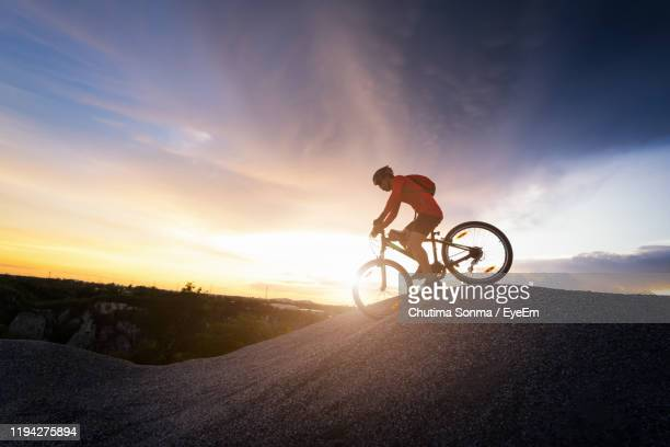 full length of man riding bicycle on mountain against sky during sunset - chonburi province stock pictures, royalty-free photos & images