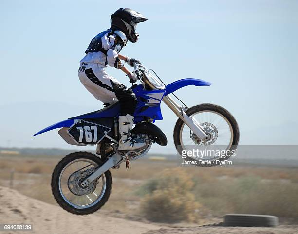 Full Length Of Man Riding Motorcycle On Sand