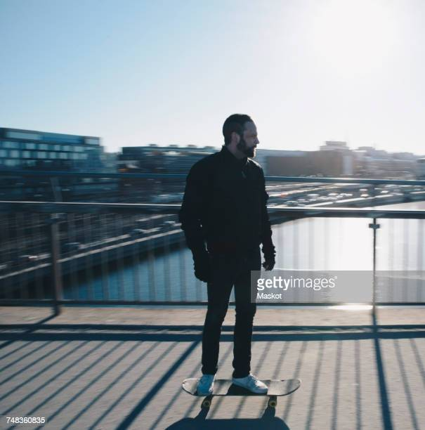 Full length of man riding skateboard on bridge in city against clear sky during sunny day