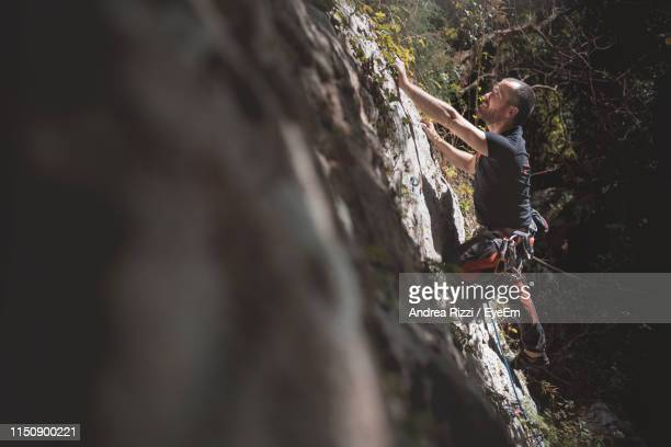 full length of man rock climbing - andrea rizzi stockfoto's en -beelden