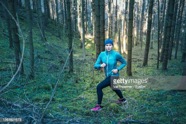 full length of man running on road in forest - val thoermer stock-fotos und bilder