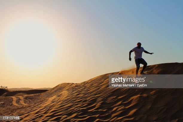 Full Length Of Man Sandboarding Against Clear Sky At Desert
