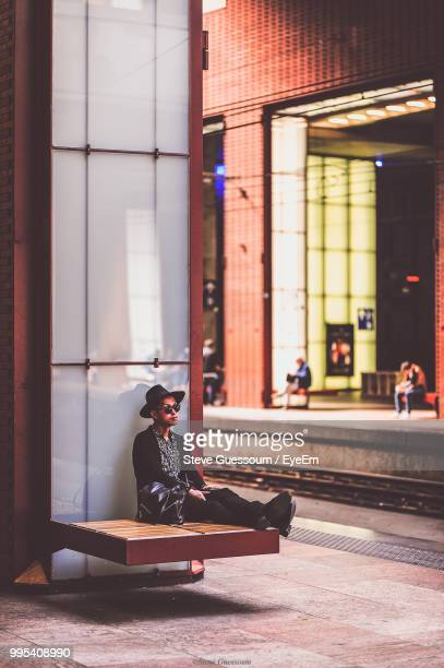 Full Length Of Man Sitting By Building In City