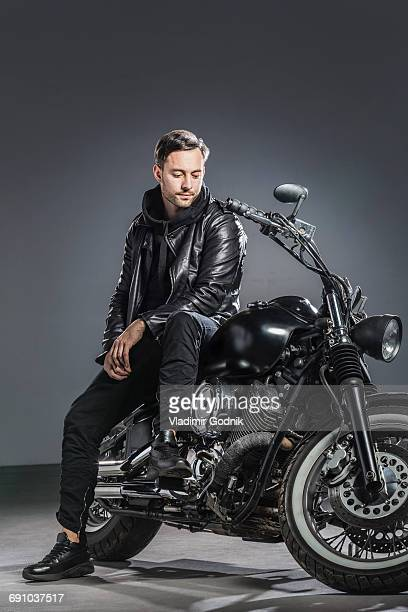 Full length of man sitting on motorcycle against gray background