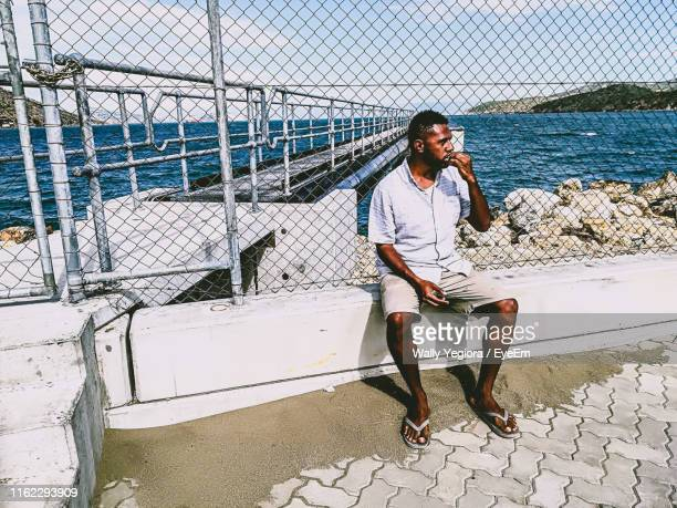 full length of man sitting on railing at sea - papua new guinea stock pictures, royalty-free photos & images