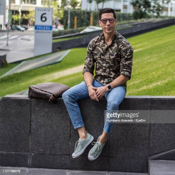 Full Length Of Man Sitting On Retaining Wall