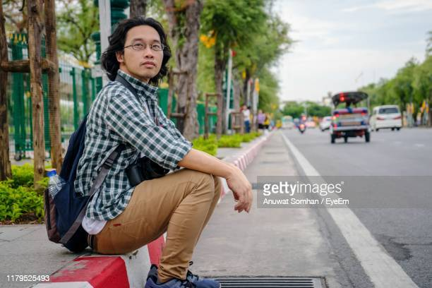 full length of man sitting on road in city - anuwat somhan stock photos and pictures