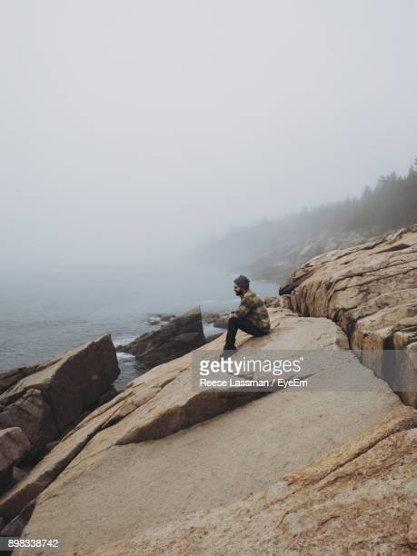Full Length Of Man Sitting On Rock By Sea Against Clear Sky