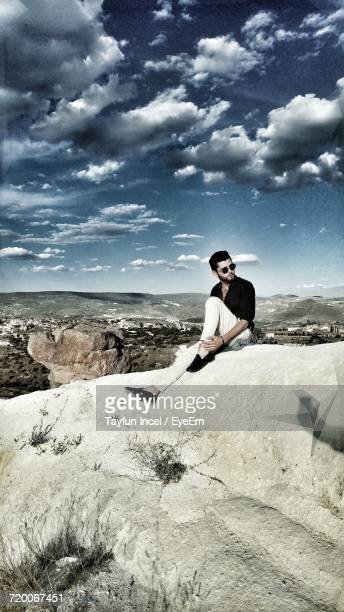 Full Length Of Man Sitting On Rock Formation At Cappadocia Against Sky