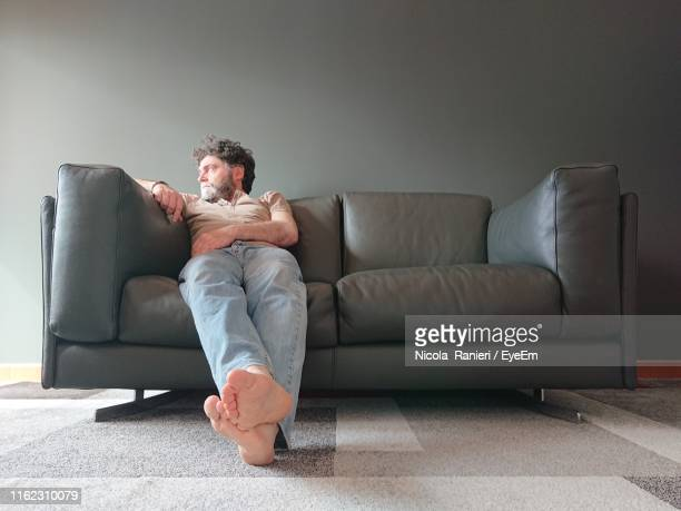 full length of man sitting on sofa at home - one man only stock pictures, royalty-free photos & images
