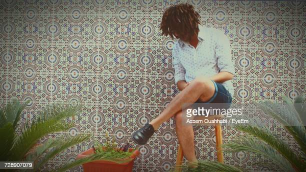 Full Length Of Man Sitting On Stool Against Tiled Wall At Yard