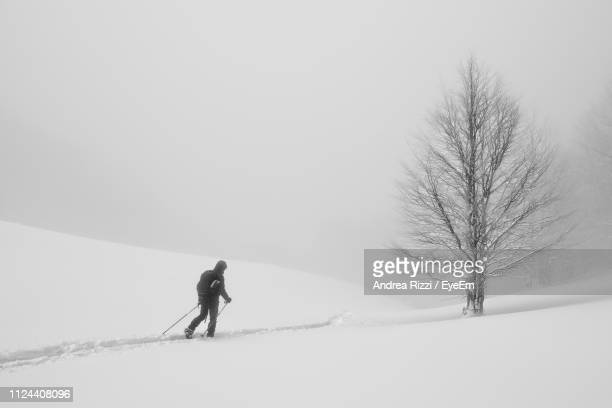 full length of man skiing on snow covered land - andrea rizzi stockfoto's en -beelden