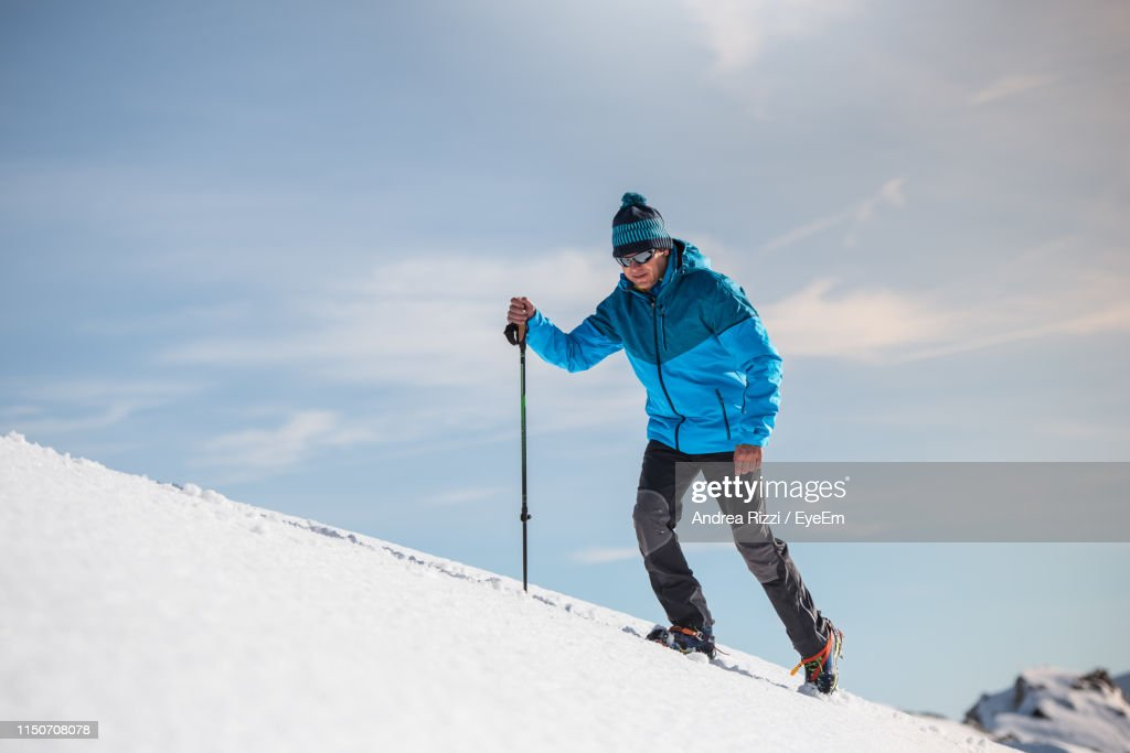 Full Length Of Man Skiing On Snowcapped Mountain Against Sky : Stock Photo