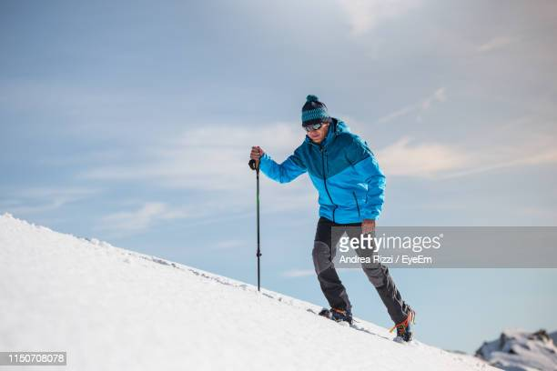 full length of man skiing on snowcapped mountain against sky - andrea rizzi stockfoto's en -beelden