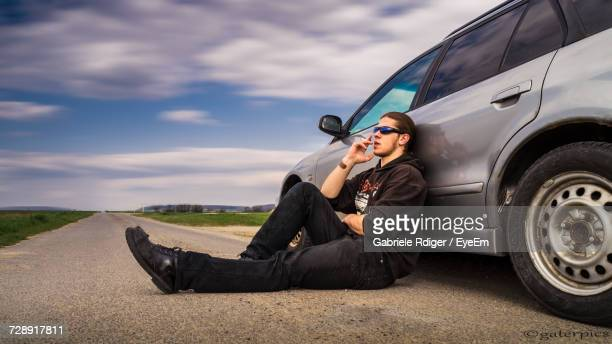 Full Length Of Man Smoking Cigarette While Relaxing By Car On Road
