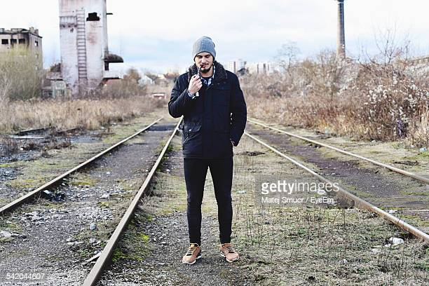 Full Length Of Man Smoking Pipe At Railroad Track