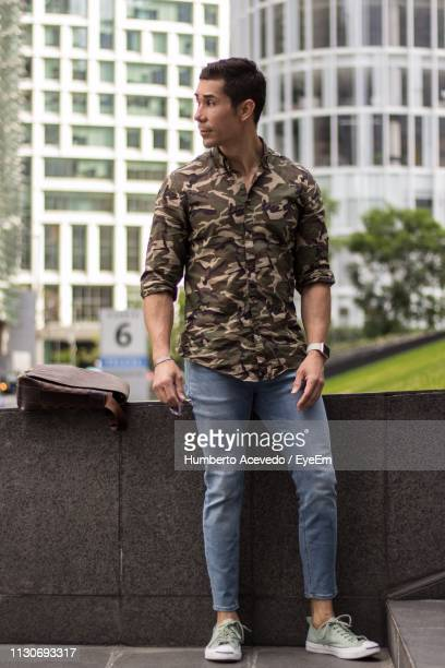 Full Length Of Man Standing Against Building In City