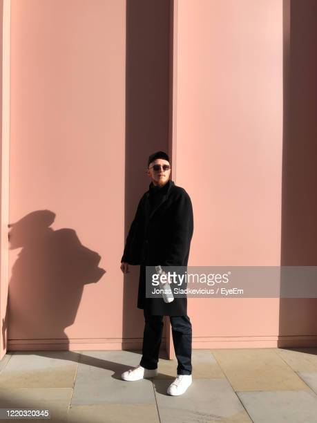 full length of man standing against building - design stock pictures, royalty-free photos & images